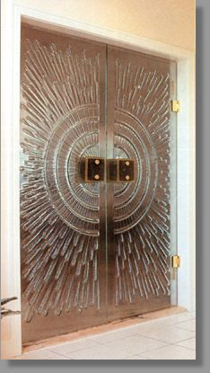 Click for a larger image. Sculptured frameless glass doors, sunburst motif, with automatic returning hinges and custom made 14k gold trim door handle.