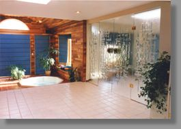 An inviting whirlpool room in a London, Ontario residence uses four attractive sculptured glass doors to provide both an emotional and functional division between the living and recreational areas.