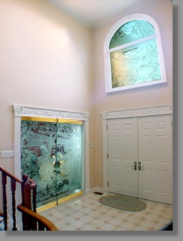 "This attractive foyer in a private home has 3/4"" (19mm) clear deep carved glass doors with a motif developed from a photograph of the client's daughter. The window above, with a complementary design, bathes the entranceway in soft, glamorous light."